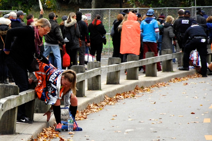 A runner is helped to the ground after finishing the ING New York City Marathon.  The finish line was in Central Park.