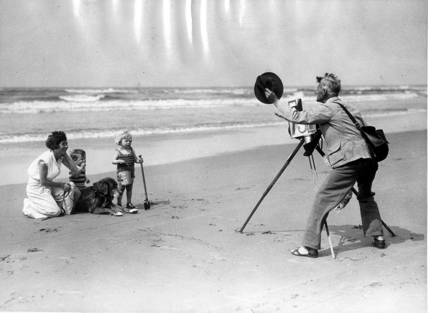 Beach photographer taking pictures of mother, children and a dog. The Netherlands, about 1930.