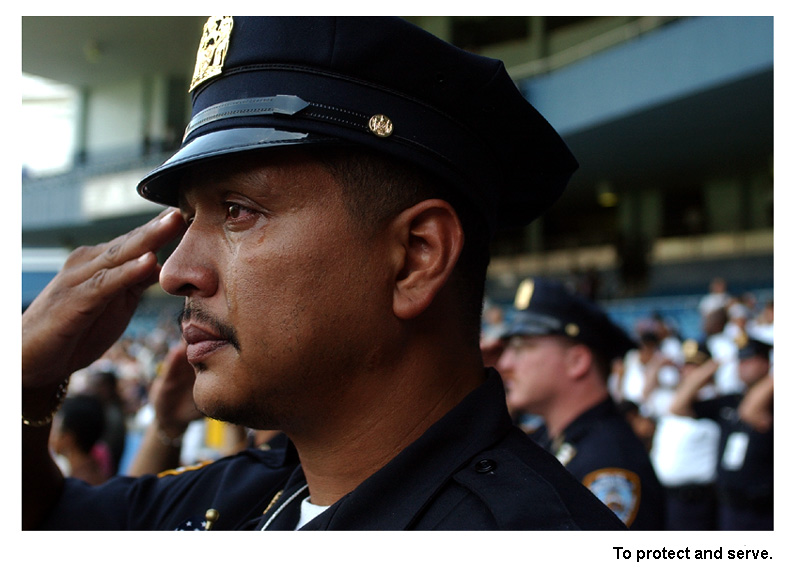 New York City Detective David Vasquez salutes while honoring his fallen comrades during a 9-11 memorial service held at Yankee Stadium.